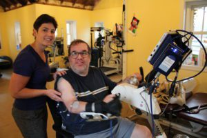 Helen is helping Tony on the Functional Electrical Stimulation (FES) bike (pictured here). The FES Bike enables clients who have suffered a stroke, with very little muscle control to exercise using pulses of electrical current to stimulate their nerves. Even if you may not be able to control your muscles, FES helps facilitate muscle activity, leading to increased range of motion, reversal of muscle atrophy, and more.